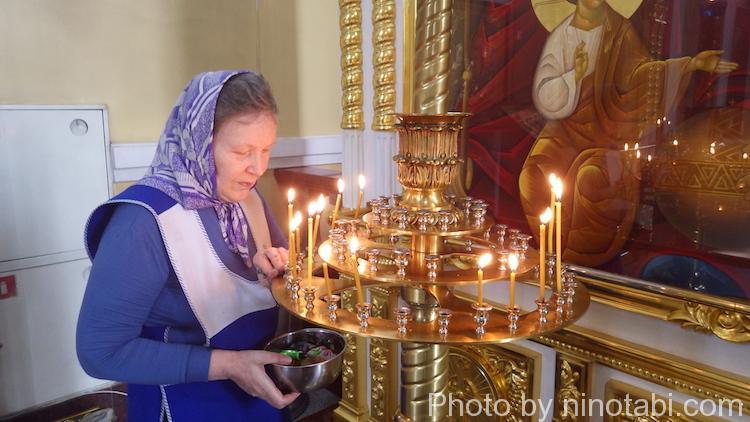 蝋を掃除して燭台を磨く女性